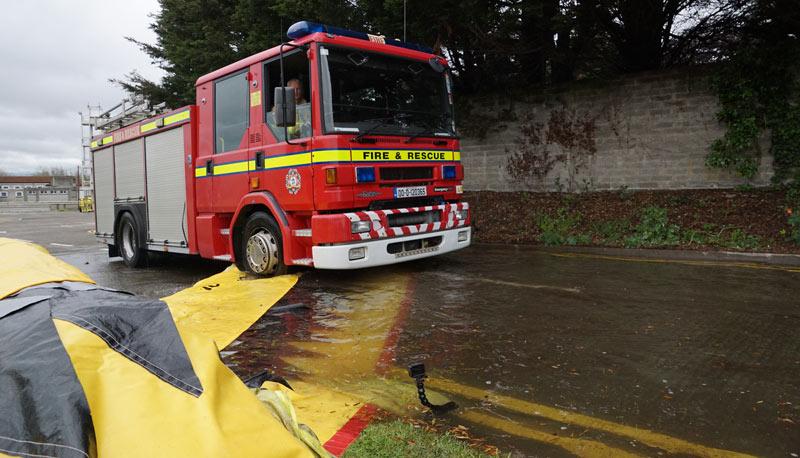 Engin de secours traversant un barrage souple anti-inondation Water-Gate rempli d'eau.