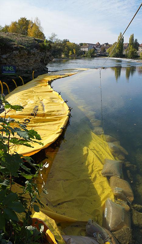 Lestage du bord d'attaque d'un batardeau souple Water-Gate©avec des buches de graviers.